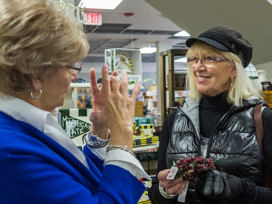 Kean's employee Sharon Cook, left, helps customer Carol Scarbrough from Leslie, at the re-opening of the store after a fire Saturday, December 5, 2015.