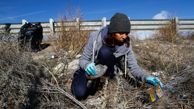 AmeriCorps member Shante Cohoe picks up trash  on Monday next to Nizhoni Park in Shiprock.
