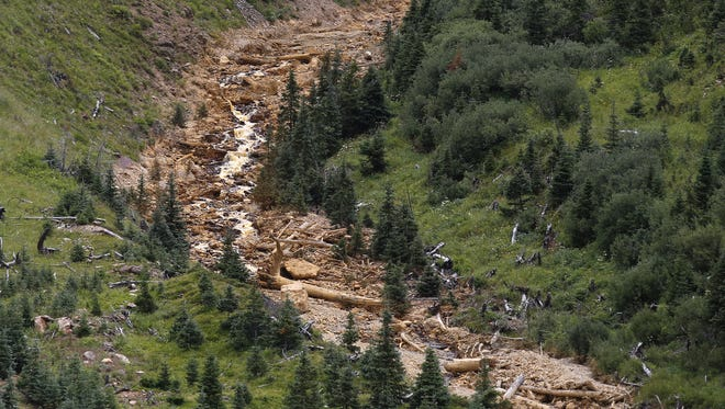 Debris from the Gold King Mine spill cascades down a mountainside north of Silverton, Colo., on Aug. 10, 2015.