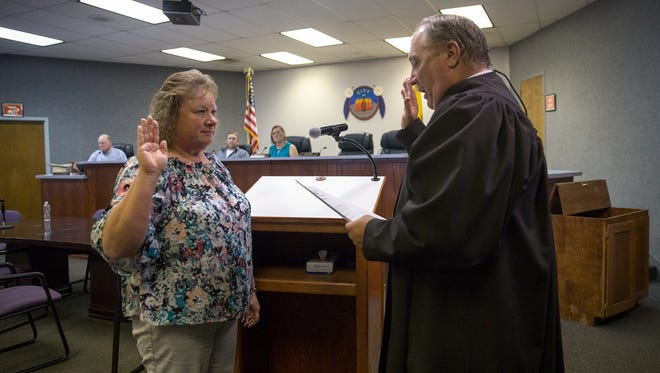 Sheri Rogers is administered the oath of office by Aztec Municipal Judge Carlton Gray Tuesday at Aztec City Hall after being reappointed to the City Commission.