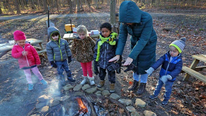 Melissa Jackson warms herself at the fire with kids during an outdoor learning time at The Orchard School, Wednesday, Dec. 6, 2017.  The northern-Indianapolis charter school commits to learning outside for at least two hours every day.