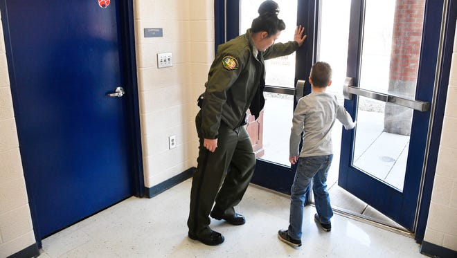 """Deputy Jamie Haynes checks to make sure the doors are locked and secure with her """"Deputy of the Day"""" Ben Spradlin. Haynes is the School Resource Officer at Franklin Elementary. Five years ago, county officials rushed to staff all elementary schools with SROs following the Sandy Hook tragedy. Tuesday Jan. 30, 2018, in Franklin, Tenn"""