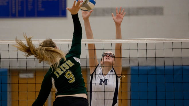Marysville junior Payton Husson blocks a spike during a regional semifinal volleyball game Tuesday, November 10, 2015 at Imlay City High School.