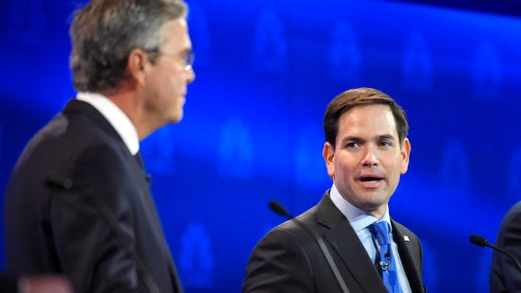 Marco Rubio, right, and Jeb Bush, argue a point during