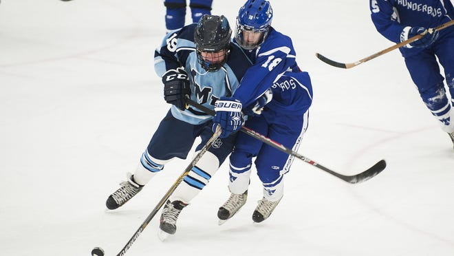 Missisquoi's Jacob Babcock (18) battles for the puck with Mount Mansfield's Patrick Burke (19) during Saturday's boys hockey game in Essex.