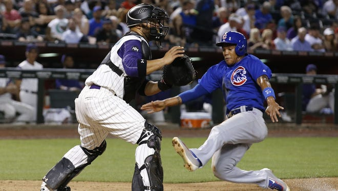 Cubs infielder Addison Russell, right, slides into home plate to score past Diamondbacks catcher Welington Castillo on April 7 in Phoenix. Russell has been on a tear as of late, hitting .381 in his last five contests.