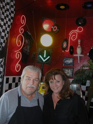 Al and Dee Anna Knauer are owners of Good Times Café, sharing a Mooney Boulevard shopping complex with Lowe's and Best Buy Electronics. The arrow behind them point to a genuine Seeburg 100 Select-O-Matic juke box that playsg 45 rpm records, two songs for a quarter.