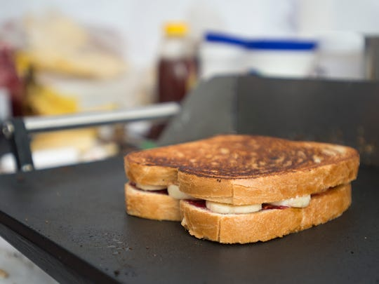 A peanut butter, jelly, honey and banana sandwich is grilled at the Cold Stone tent on the last day of the Taste of Fort Collins festival Sunday, June 15 2014.