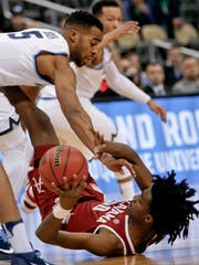 Alabama's Herbert Jones, bottom, tries to p[ass from the floor as Villanova's Phil Booth (5) defends during the first half of a second-round game in the NCAA men's college basketball tournament, Saturday, March 17, 2018, in Pittsburgh. (AP Photo/Keith Srakocic)