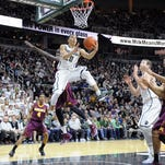 MSU's Travis Trice splits the Minnesota defense for a shot in the first half Thursday night at Breslin Center.
