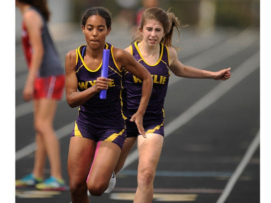 Wylie's Abbigayle Gollihar hands off the baton to Brianna Douglas on the second leg of the girls 1600m relay during the District 5-4A track meet on Thursday, April 13, 2017, at Wylie's Bulldog Stadium.