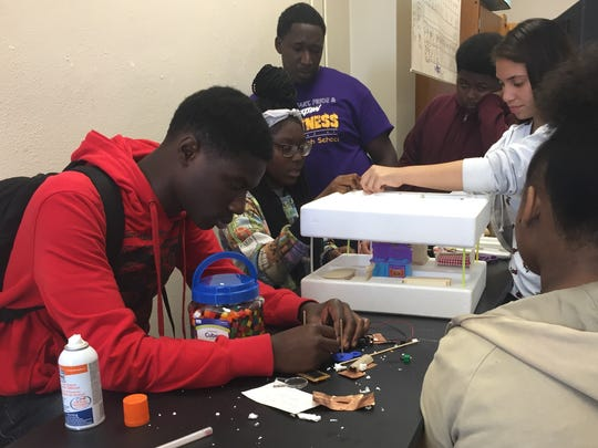 Wossman High School students led by teacher Ortadius Brass (center, purple shirt) work on a house that will be wired with electricity as part of a science and technology class.