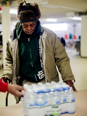 Louis Brown, 80, of Flint  receives a case of free bottled water from the North End Soup Kitchen at 735 E. Stewart Ave. in Flint  Wednesday, Jan. 13, 2016. He says he is worried about this entire water situation.