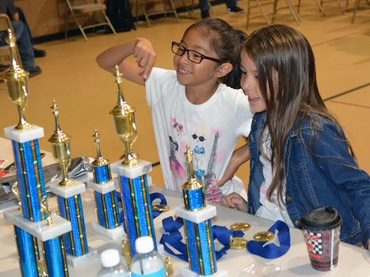 Angelita Ontiveros, left, and Mia Allison, right, look over the trophies prior to the start of  a chess tournament, which brought in teams from the Las Cruces and El Paso area on Oct. 8, 2016.