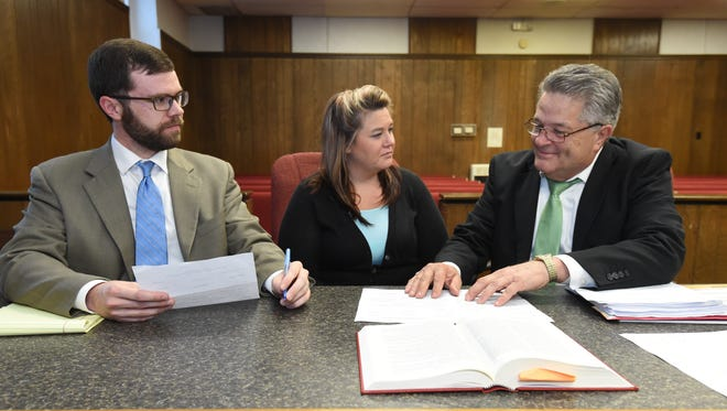 Ashley Giles, center, confers with her defense attorneys Erwin Davis, right, and Aaron Cash, left, Thursday in Marion County Circuit Court. Giles, a former Marion County Extension employee, faces seven counts of forgery and one count of theft by deception.