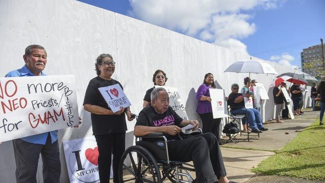 Retired priest Joe San Agustin leads a prayer during the Concerned Catholics of Guam silent protest across the street from the Cathedral Basilica in Hagatna on Dec. 20, 2015.