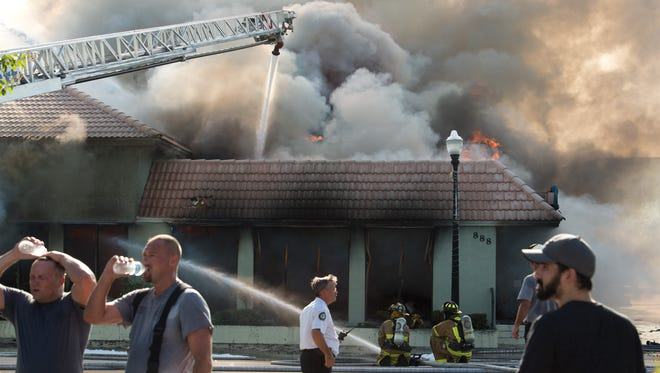 Firefighters cool off with water as fire guts the Nobile Shoes store July 27, 2016, at the store's location near the corner of U.S. 1 and Colorado Avenue in downtown Stuart.