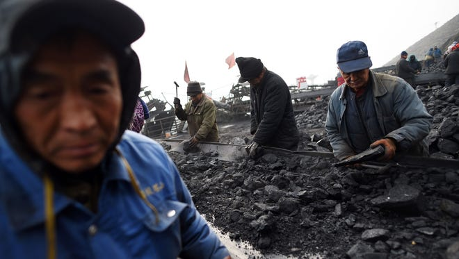 In this file photo taken on Nov. 20, 2015, workers sort coal on a conveyer belt, near a coal mine at Datong, in China's northern Shanxi province.