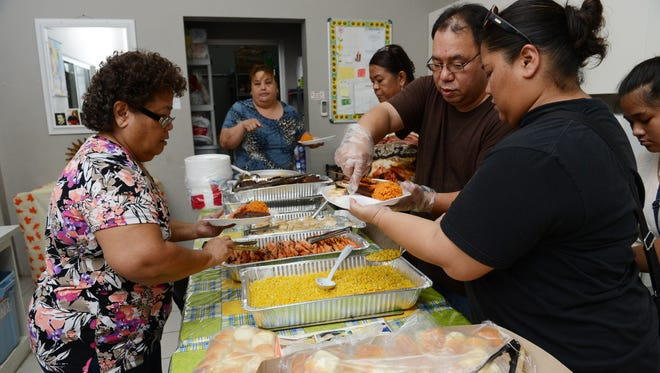 In this November 2013 file photo, members of the Cepeda family, familian Golo, of Toto, serve Thanksgiving meals to those in need at Kusinan Kamalen Karidat.