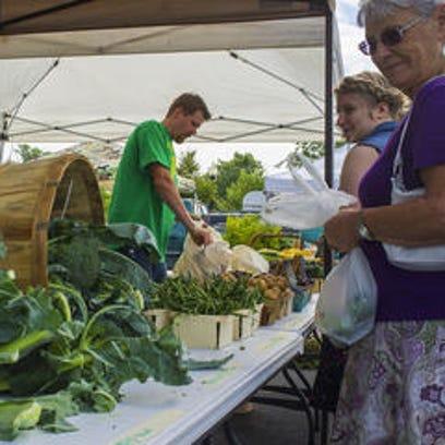 People shop the Williamston Farmers Market in July