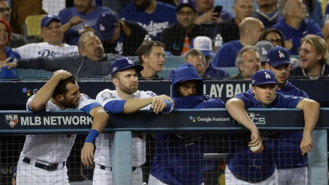 Some Los Angeles Dodgers watch from the dugout during the ninth inning of Game 3 of the National League Championship Series baseball game against the Milwaukee Brewers Monday, Oct. 15, 2018, in Los Angeles. (AP Photo/Matt Slocum)
