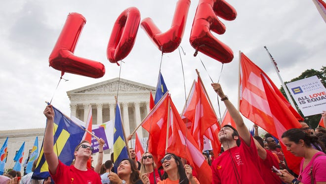 """Same-sex marriage supporters hold up balloons that spell the word """"love"""" as they wait outside of the Supreme Court in Washington in June 2015.."""