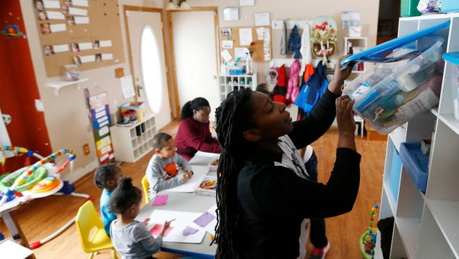 Tonja Boggs pulls out glue from a bin of supplies Feb. 11, 2016, as children work on a craft project at her in-home day care in Des Moines.