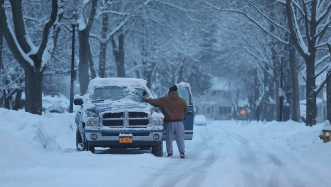 Jerald Brown clears snow off his truck before driving away from Elmdorf Ave. in Rochester.