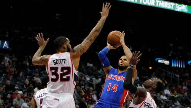 Pistons guard D.J. Augustin (14) shoots the ball over the Hawks forward Mike Scott and guard Dennis Schroder (17) in the second quarter tonight in Atlanta.