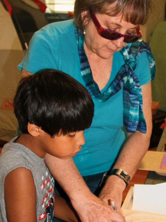 MADDY HAYDEN - CURRENT-ARGUS   Dr. Carol Williford helps Noah Lopez draw a grid to practice fine motor skills.