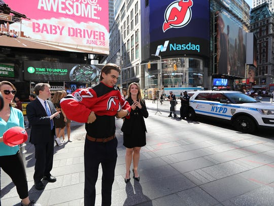 Nico Hischier puts on a Devils jersey in Times Square