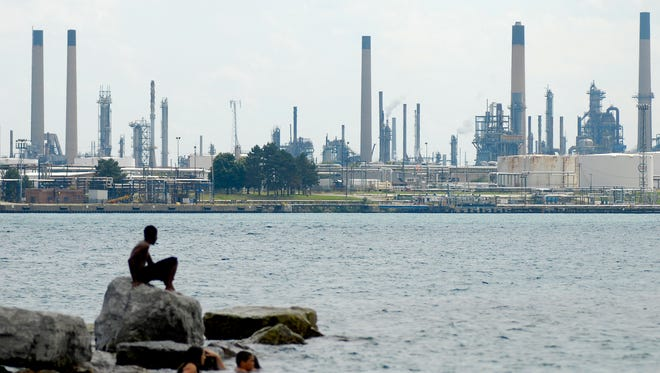 Factory towers rise above the horizon as children swim in the St. Clair River, Monday, Aug 25 along the Blue Water River Walk in Port Huron.