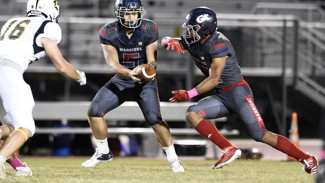 Grovetown quarterback Hunter Thomason hands off to Joseph Jean during football action against Evans at Grovetown High School in Grovetown, Ga., Friday evening October 16, 2020