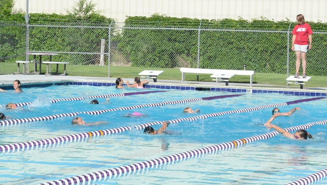 The younger Desert Fish Swim Team members swim the freestyle the length of the pool under the direction of coach Dawnitta Neely during practice Monday morning. They are preparing for Saturday's opening meet.