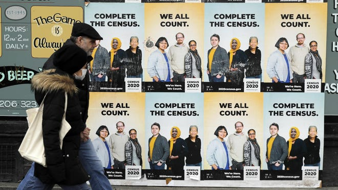 People walk past posters encouraging participation in the 2020 Census, Wednesday, April 1, 2020, in Seattle's Capitol Hill neighborhood. Wednesday is Census Day, the date used to reference where a person lives for the once-a-decade count, as the U.S. is almost paralyzed by the spread of the novel coronavirus, but census officials vowed the job would be completed by its year-end deadline.