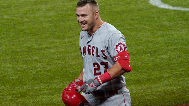 Los Angeles Angels' Mike Trout smiles as he approaches the dugout after hitting a solo home run in the fifth inning of a baseball game against the Texas Rangers in Arlington, Texas, Thursday, Sept. 10, 2020. (AP Photo/Tony Gutierrez)