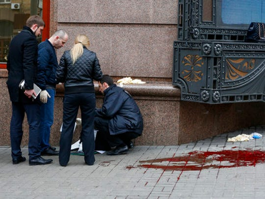 Forensic experts and police officers examine the scene following the killing of Denis Voronenkov in Kiev, Ukraine, Thursday, March 23, 2017. Ukrainian police said Voronenkov was shot dead Thursday by an unidentified gunman at the entrance of an upscale hotel in the Ukrainian capital. Voronenkov, 45, a former member of the communist faction in the lower house of Russian parliament, had moved to Ukraine last fall and had been granted Ukrainian citizenship.