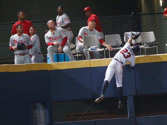 Atlanta Braves left fielder Chase d'Arnaud (23) climbs the wall in front of the Philadelphia Phillies' bullpen but can't get a foul ball hit by Phillies' Maikel Franco during the seventh inning of a baseball game Thursday, July 28, 2016, in Atlanta,. Philadelphia won 7-5. (AP Photo/John Bazemore)