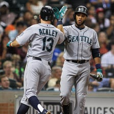 Sep 19, 2014; Houston, TX, USA; Seattle Mariners left fielder Dustin Ackley (13) celebrates with second baseman Robinson Cano (22) after hitting a home run during the third inning against the Houston Astros at Minute Maid Park. Mandatory Credit: Troy Taormina-USA TODAY Sports
