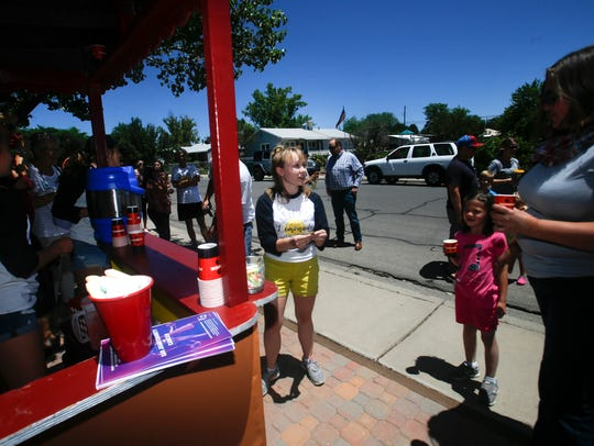 Keely Stockham, center, talks with customers Tuesday at Keely's Lemonade Stand on North Orchard Avenue in Farmington.