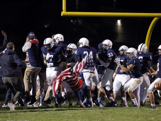 East Lansing players celebrate their win over Holt