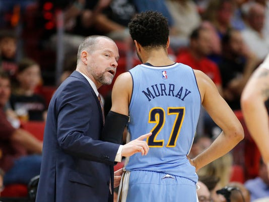 Denver Nuggets head coach Michael Malone, left, talks to Jamal Murray (27) during the first half of an NBA basketball game against the Miami Heat, Sunday, April 2, 2017, in Miami, Fla. (AP Photo/Joel Auerbach)