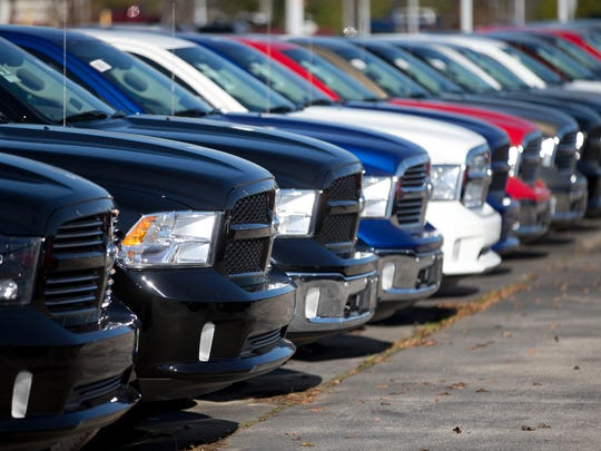 Ram pickup trucks are on display on the lot at Landmark Dodge Chrysler Jeep RAM in Morrow, Ga. Investors will be watching third-quarter earnings from General Motors, Fiat Chrysler and Ford this week for clues of whether the auto industry's six-year expansion is cooling or starting to end.