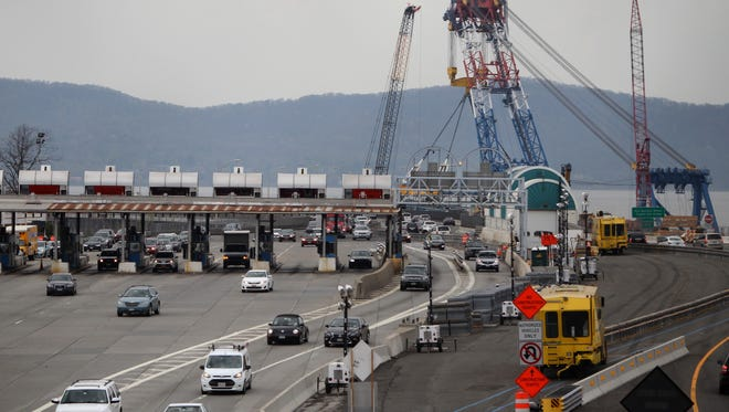 The Left Coast Lifter works near the Tarrytown shore as traffic moves through the old tollgates on the Tappan Zee Bridg.