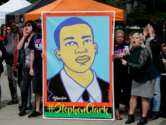In this April 9, 2018, file photo protesters display an image of Stephon Clark at a crime victims rights rally, at the Capitol in Sacramento, Calif.