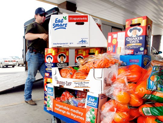 Ross Hodges helps load a trailer full of food donated