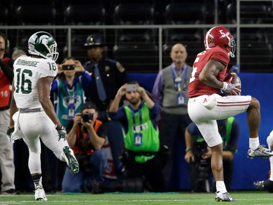 Alabama defensive back Cyrus Jones intercepts the ball as MSU wide receiver Aaron Burbridge looks on during the first half of the Cotton Bowl.