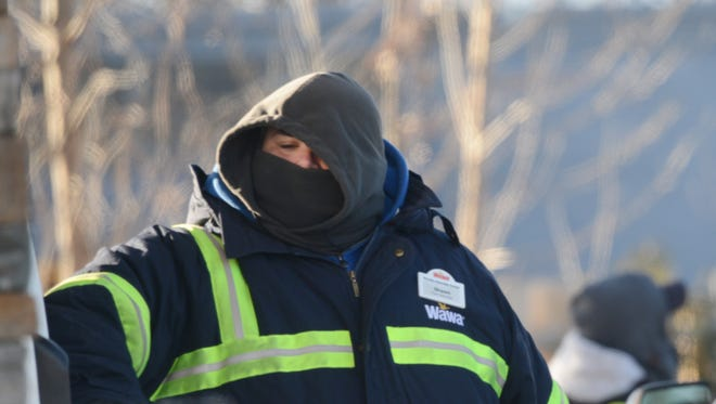 An attendant braves the cold at a gas station in Hackensack