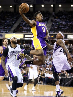 Los Angeles Lakers small forward Nick Young (0) goes up for a basket between Sacramento Kings center DeMarcus Cousins (15) and point guard Isaiah Thomas (22) before goal tending is called during the second quarter at Sleep Train Arena.