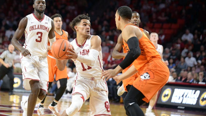 Oklahoma guard Trae Young (11) drives to the basket in front of Oklahoma State  guard Kendall Smith (1) during the second half at Lloyd Noble Center.